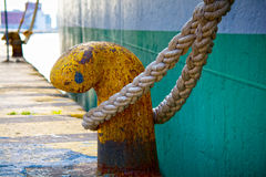 Bollard with rope. Οld rusted mooring bollard with rope. Side view of an old cargo ship at the background royalty free stock photo