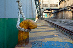 Bollard with rope. Οld rusted mooring bollard with rope. Side view of an old cargo ship and an old abandoned factory at the background royalty free stock image