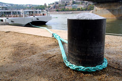 Bollard with rope in a harbor Stock Images
