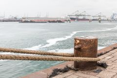 A bollard with rope on a quay in the harbor stock photography