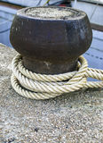 Bollard. A rope tied around a bollard to attach a boat stock photos