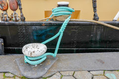 Bollard with rope. Royalty Free Stock Image