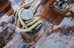 Bollard with a rope on the wooden deck of a sailing vessel, clos royalty free stock image