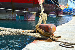 Bollard and ropes. View of a mooring bollard at the dock and cargo vessels at the background royalty free stock image
