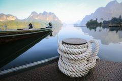 Bollard on sea water, rope for mooring a vessel is adhered to a pier royalty free stock photo