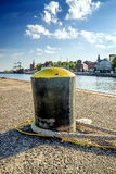 Bollard in a seaport with sailing ship Stock Image