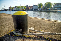 Bollard in a seaport with sailing ship Stock Images