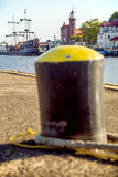 Bollard in a seaport with sailing ship Royalty Free Stock Photos