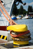 Bollard securing ship with line. Yellow strong metal bollard and ship secured with mooring ropes Stock Photos
