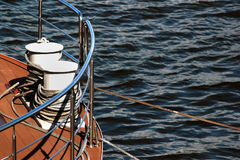 Bollard on ship deck with metal mooring lines. Royalty Free Stock Image