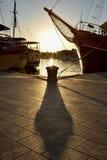 Bollard and ships in contralight. Ships and bollard in Makarska marina during sunset Stock Images