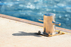Bollard in sunlight at a jetty. Bollard made out of steel in sunlight and glittering water in background Royalty Free Stock Photo