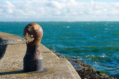 Bollards against a blue sky. Bollards to moor ships in an old harbour Royalty Free Stock Image