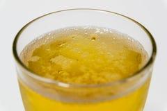 Bolle bianche dorate della birra nel vetro Immagine Stock