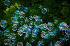 Bolle dell'arcobaleno dal ventilatore della bolla nel parco immagini stock