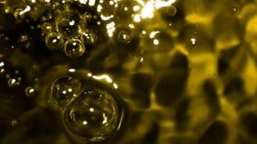 Bolle di aria di Bokeh in acqua su fondo nero e dorato Fotografia Stock Libera da Diritti