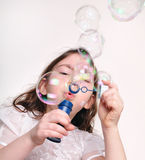 Bolle di salto del bambino con la bacchetta della bolla Fotografia Stock
