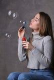 Bolle di salto della bionda Fine in su Fondo grigio Fotografia Stock