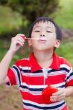 Bolle di sapone di salto del bambino asiatico nel parco di estate, backgrou della natura Immagini Stock