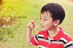 Bolle di sapone di salto del bambino asiatico nel parco di estate, backgrou della natura Fotografia Stock