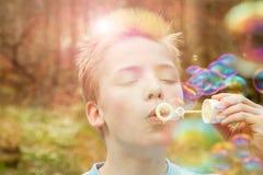 Bolle di sapone di salto del giovane ragazzo all'aperto Fotografia Stock