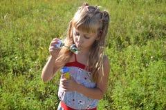 Bolle di sapone di salto della bambina Fotografia Stock