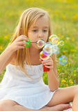 Bolle di sapone di salto della bambina sveglia Fotografie Stock Libere da Diritti