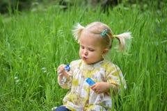 Bolle di sapone di salto della bella neonata nel parco Immagine Stock