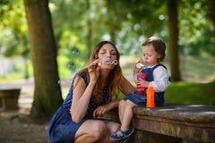 Bolle di sapone di salto figlia della piccola e della bella madre in somma fotografie stock