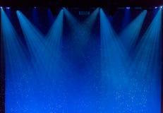 Bolle e raggi di luce blu attraverso il fumo in scena Immagine Stock