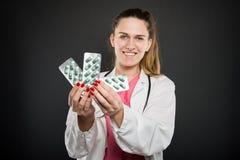Bolle sorridenti della tenuta del dietista femminile delle pillole Immagine Stock