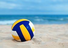 Bollen ligger på sand nära havet royaltyfri fotografi