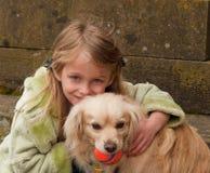 bollhundflicka som kramar litet barn Arkivfoto