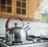Bollitore che bolle su una stufa di gas nella cucina Immagini Stock
