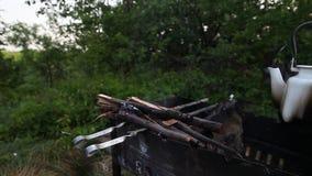 Bollitore che si siede su un barbecue di campeggio stock footage