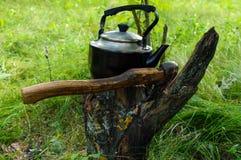 Bollitore d'annata per acqua di riscaldamento e un'ascia, contro il contesto della natura Stile degli uomini Fotografia Stock