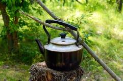 Bollitore d'annata per acqua di riscaldamento su un vecchio ceppo nei precedenti della natura Stile degli uomini Fotografia Stock