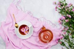 Bollitore di vetro, tazza da the con tè sulla sciarpa e mazzo rosa delle margherite fotografia stock libera da diritti