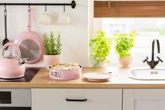 Bollitore e dolce rosa sul controsoffitto di legno nel inte luminoso della cucina fotografia stock
