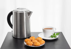 Bollitore elettrico, tazza di tè e biscotti su una tavola immagini stock