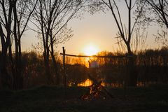 Bollitore sopra il fuoco sul lago nella sera immagini stock