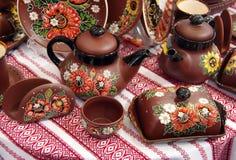 Bollitori ceramici dei piatti delle tazze sulla tovaglia Fotografie Stock
