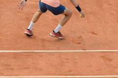 Bollkalle som pipcking upp balen på tennisbanan Royaltyfri Foto