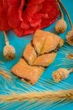 Bollo apetitoso con la amapola adornada con una flor ciánica en un azul Imagen de archivo