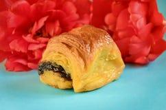 Bollo apetitoso con la amapola adornada con una flor ciánica en un azul Imagenes de archivo