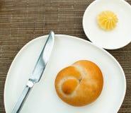 Bollo con mantequilla en la placa blanca Imágenes de archivo libres de regalías