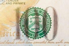 Bollo del dipartimento del Ministero del Tesoro su cento macro del primo piano della fattura di dollaro americano Fotografia Stock Libera da Diritti