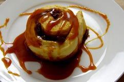 bollo del Pasa-canela cubierto con la salsa pegajosa del caramelo imagen de archivo