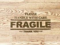 Bollo fragile di parola sul fondo di legno della plancia Immagine Stock Libera da Diritti