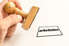 Bollo su un fondo bianco circa disoccupazione con la parola tedesca per i disoccupati fotografia stock libera da diritti